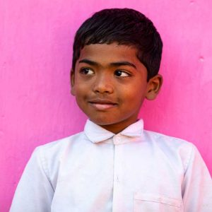 Photograph of a boy in India wearing a white shirt leaning against a bright pink background
