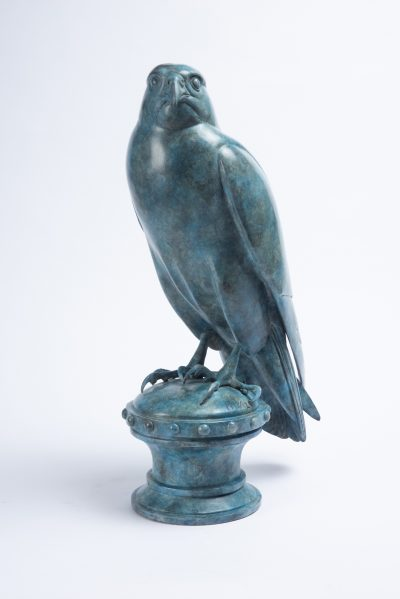 a painted bronze sculpture of a peregrine falcon